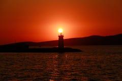 Farol mostrado em silhueta contra um por do sol Foto de Stock Royalty Free