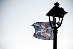Farola negra en silueta con la bandera de pirata fotografía de archivo libre de regalías