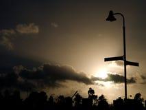 Farola silueteada por el Sun, en el cielo oscuro Foto de archivo