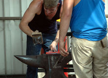 Farrier working on red hot horseshoe. Farrier working on a red hot shoe on his anvil Royalty Free Stock Images