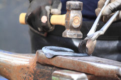 Farrier making a horseshoe. A farrier is making a horseshoe hitting with a hammer on the anvil Stock Photography
