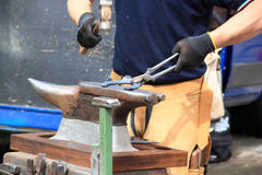 Farrier making a horseshoe. A farrier is making a horseshoe hitting with a hammer on the anvil Royalty Free Stock Images