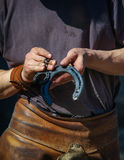 Farrier showing horsehoes Royalty Free Stock Images