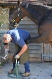 Farrier som arbetar på en häst Fotografering för Bildbyråer