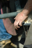 Close-up of farrier using file on horse shoe close Royalty Free Stock Photography