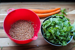 Farro Grain being readied for a Summer Salad. Fresh carrots, arugula in a red bowl stock photography