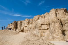 Group of people listening to a guide about information and history of the Naqsh-e Rustam. royalty free stock photography