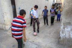 Iranian teenagers playing football in a courtyard, Shiraz, Iran. Fars Province, Shiraz, Iran - 18 april, 2017: Children playing football in a courtyard royalty free stock images