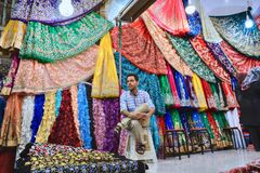 Lone dealer sits on banquette in textile department on bazaar. Royalty Free Stock Image