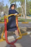 Muslim woman in hijab during morning exercise at outdoor gym. Royalty Free Stock Images