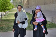 Two Muslim women in hijabs are walking with a child. Fars Province, Shiraz, Iran - 19 april, 2017: A Muslim family, a young woman, a mature woman and a little Stock Photo