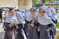 School uniform Iranian school girls with hijab and head visor. royalty free stock image