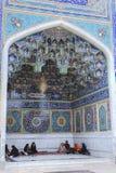 Islamic parishioners sit on carpet in deepening of mosque buildi. Fars Province, Shiraz, Iran - 19 april, 2017: Shah Cheragh complex, Muslim parishioners sit on Royalty Free Stock Photos
