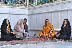Muslims are sitting on carpet in niche of mosque building. Fars Province, Shiraz, Iran - 19 april, 2017: Shah Cheragh Shrine,  group of muslims pilgrims rests Stock Photography