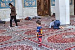 Courtyard of Iranian mosque, Muslims pray, sleeping, walk, Shira. Fars Province, Shiraz, Iran - 19 april, 2017: Shah Cheragh Shrine, A little boy is talking on a Royalty Free Stock Photos