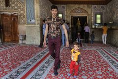 Muslim family, father and son leave the mosque, Shiraz, Iran. Fars Province, Shiraz, Iran - 19 april, 2017: Shah Cheragh Shrine, A man leaves the mosque after a Stock Photo