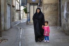 Muslim woman in chador stands in courtyard with little girl. Royalty Free Stock Image