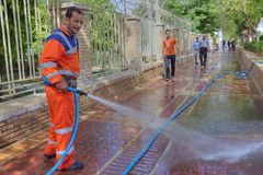Street cleaner uses pressurized water for washes pavement, Shira. Fars Province, Shiraz, Iran - 19 april, 2017: Street worker washes the pavement, using a hose Stock Images