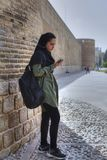 Girl in hijab listen to music from smartphone through earphones. Fars Province, Shiraz, Iran - 19 april, 2017: A teenage girl in a Muslim hijab stands at the Stock Photos