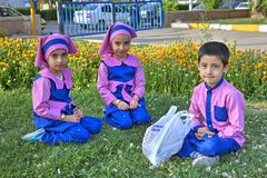 Preschool children are sitting on lawn grass in park, Iran. Fars Province, Shiraz, Iran - 19 april, 2017: Three preschool children, two girls and one boy Stock Images