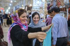 Women in hijab choose fabric in city market, Shiraz, Iran. Royalty Free Stock Image