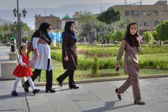 Muslim women are walking in center of city, Shiraz, Iran. Fars Province, Shiraz, Iran - 19 april, 2017: Women in hijabs walk along the city street Stock Photography