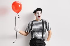 Fars som rymmer en röd ballong och lutar mot väggen arkivbild
