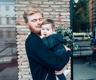 Farsa med en liten son i hans armar Arkivbilder