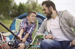 Farsa med hans son som tillsammans fiskar royaltyfria bilder