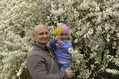 Farsa med lite dottern i hennes armar som på våren står nära ett blomma träd royaltyfri bild