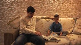Farsa med svart hår i en vit tröja och lite son i en blått som är randig, blick på encyklopedien som sitter på ett mjukt lager videofilmer
