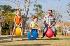 Farsa och barn som spelar på gräsmattan Royaltyfria Foton