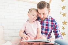 Farsa och dotter att sitta tillsammans och läsa en bok arkivfoton