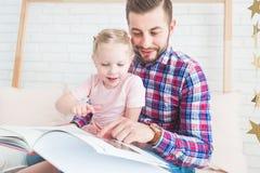 Farsa och dotter att sitta tillsammans och läsa en bok royaltyfria bilder