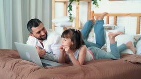 Farsa och gullig liten flickaklockatecknad film på hemmastadda lögner för bärbar dator på säng, ultrarapid stock video