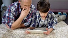 Farsa och hans son som lär hur man använder den nya minnestavlan, modern teknologi, closeness arkivbilder
