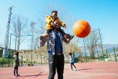 Farsa och liten son som spelar basket royaltyfri fotografi