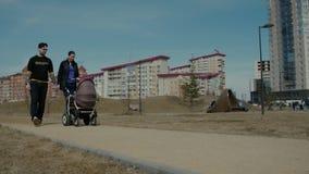 Farsa och mamma som går med en stoller arkivfilmer
