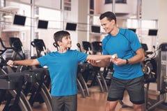 Farsa och son i den samma kläderna i idrottshall Fadern och sonen leder en sund livsstil Fotografering för Bildbyråer