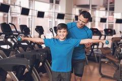 Farsa och son i den samma kläderna i idrottshall Fadern och sonen leder en sund livsstil Royaltyfria Bilder