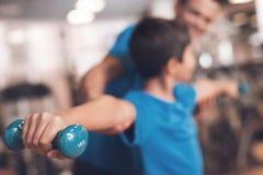 Farsa och son i den samma kläderna i idrottshall Fadern och sonen leder en sund livsstil Arkivfoton