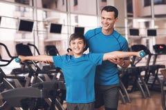 Farsa och son i den samma kläderna i idrottshall Fadern och sonen leder en sund livsstil Royaltyfri Bild