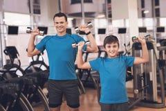 Farsa och son i den samma kläderna i idrottshall Fadern och sonen leder en sund livsstil Arkivbild