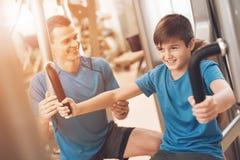 Farsa och son i den samma kläderna i idrottshall Fadern och sonen leder en sund livsstil royaltyfri fotografi