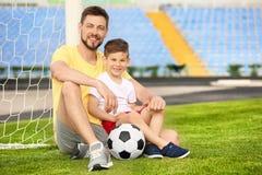 Farsa och son med fotbollbollen fotografering för bildbyråer