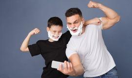 Farsa och son som har gyckel tillsammans och att posera med att raka skum fotografering för bildbyråer