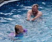 Farsa och son som spelar i simbassängen Royaltyfri Bild