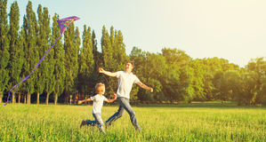 Farsa- och sonbarn som flyger en drake i sommarnatur Royaltyfria Bilder