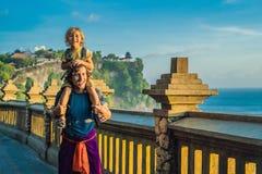 Farsa- och sonhandelsresande i den Pura Luhur Uluwatu templet, Bali, Indonesien Fantastiskt landskap - klippa med blå himmel och  royaltyfri fotografi