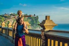 Farsa- och sonhandelsresande i den Pura Luhur Uluwatu templet, Bali, Indonesien Fantastiskt landskap - klippa med blå himmel och  royaltyfri bild